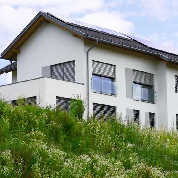Weißes Haus auf Grashügel mit Photovoltaik am Dach