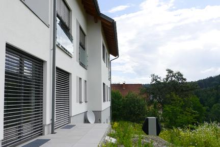 Seitenansicht Haus mit Wärmepumpe in Wiese und Satelitenschüssel