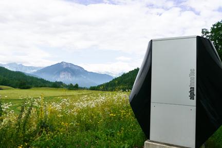 waermepumpe vor einer grünen wiese mit bergen im hintergrund