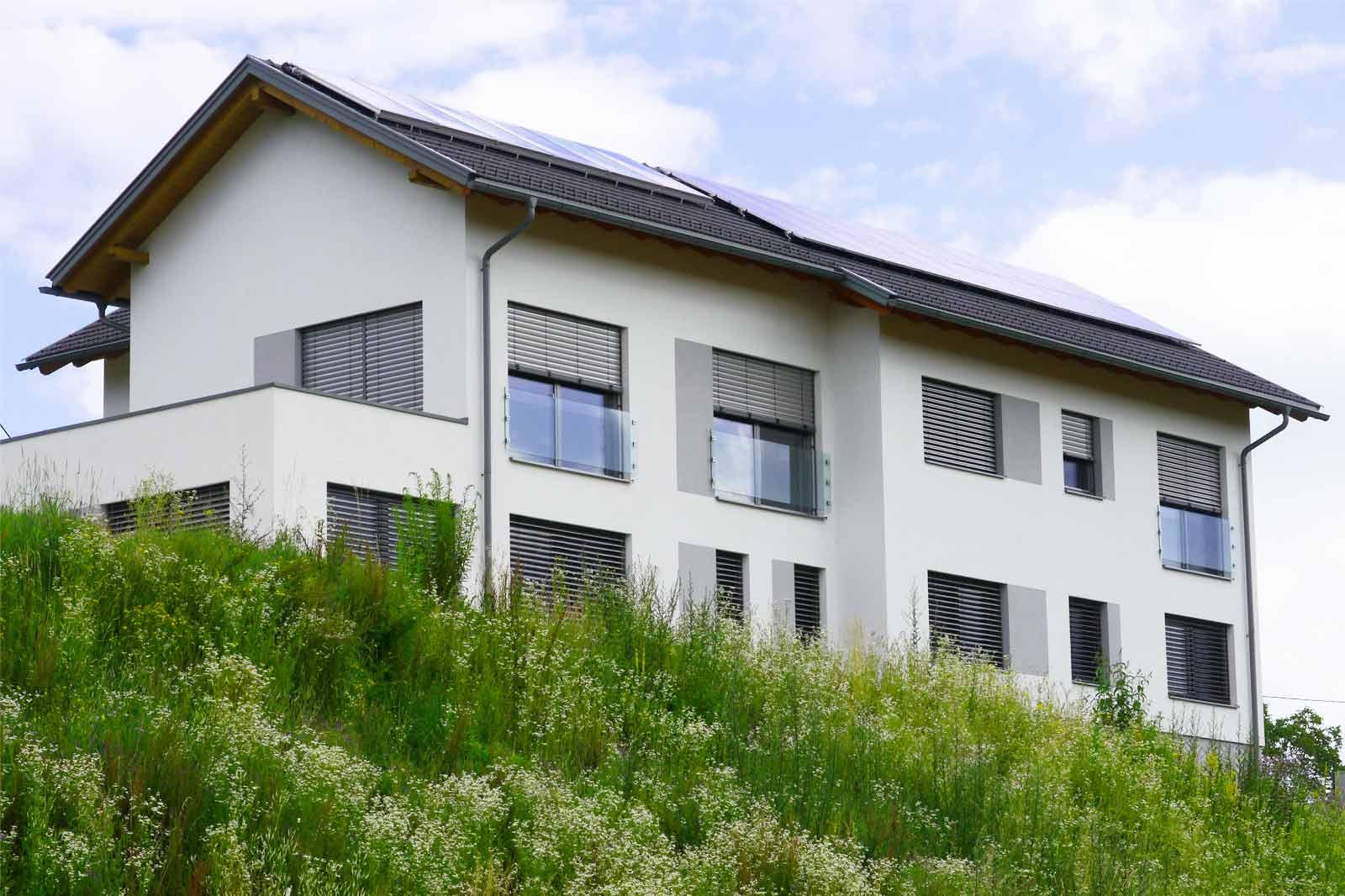 Zweifamilienhaus auf Grashügel mit Solaranlage und Photovoltaik am Dach