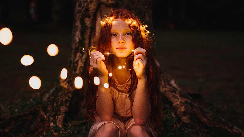 Mädchen mit leuchtender Lichterkette in Wald