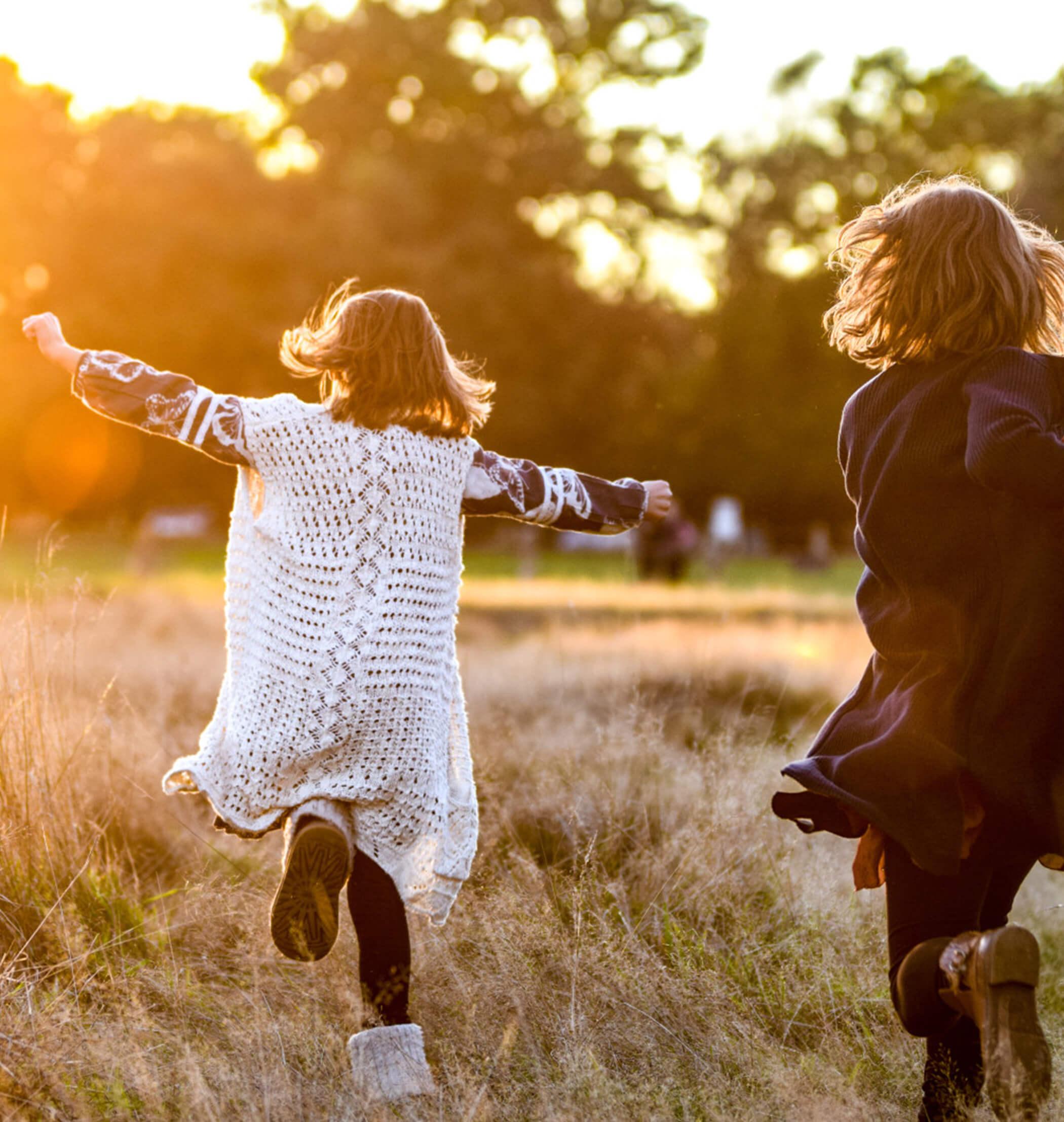 Zwei Kinder laufen spielend durch Wiese