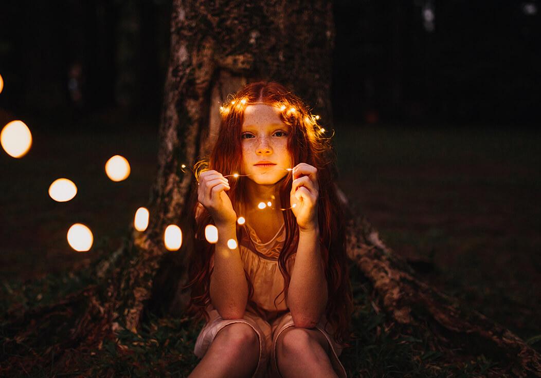 Mädchen mit leuchtender Lichterkette im Wald