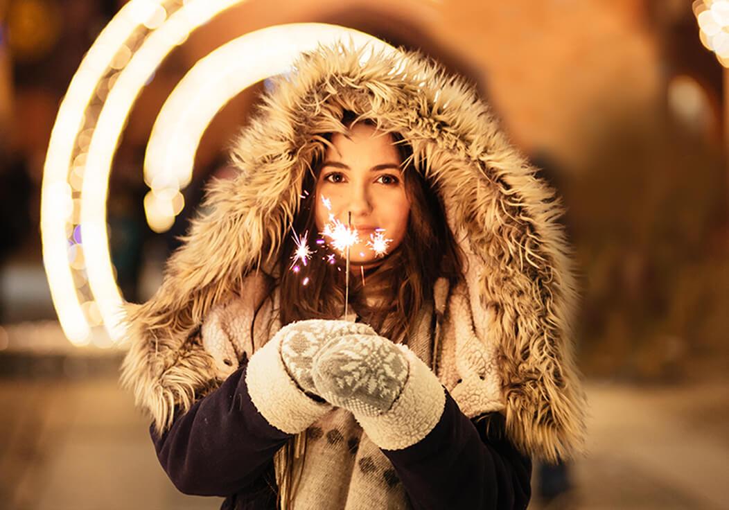 Frau im Winter umgeben von Licht und Wärme