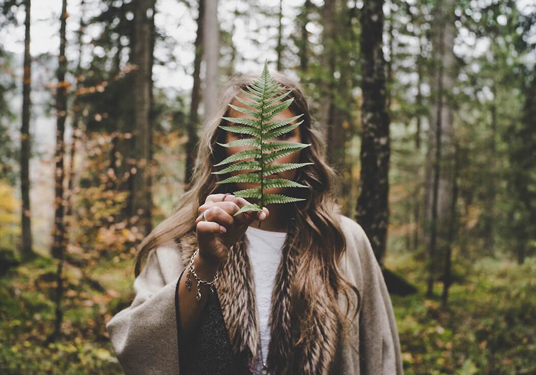 Frau im Wald mit einem Farnblatt vorm Gesicht