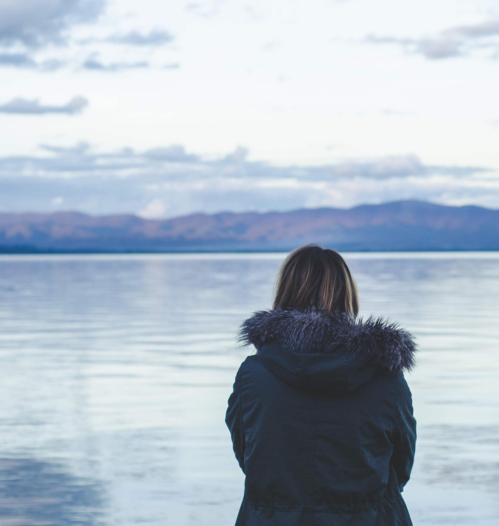 Frau am See sieht in die Ferne