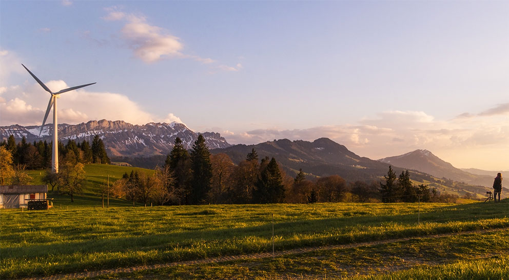 Berglandschaft mit Windturbine und Solaranlage