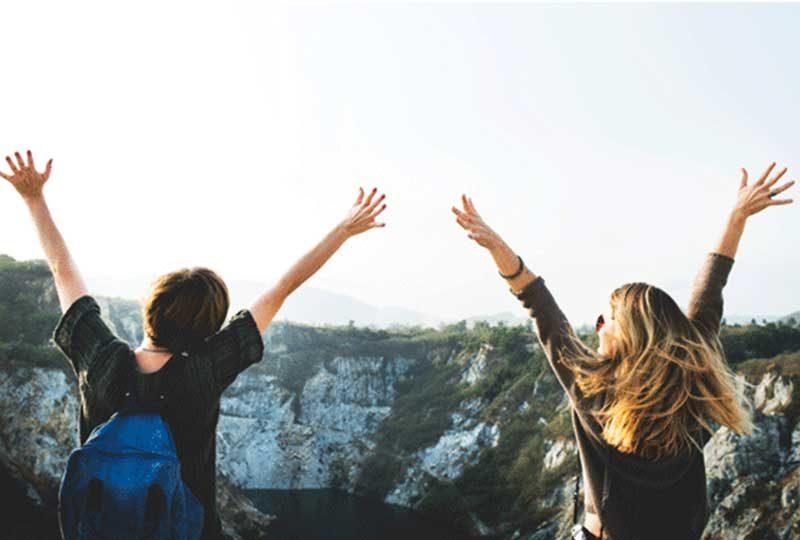 Zwei Frauen in Jubelpose auf einem Berg