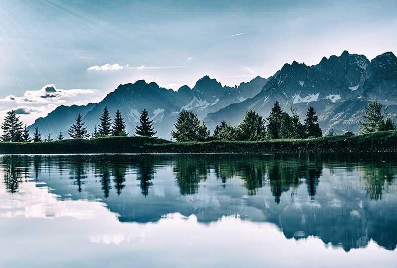 Klarer Bergsee mit Gebirgskette und Sonne im Hintergrund