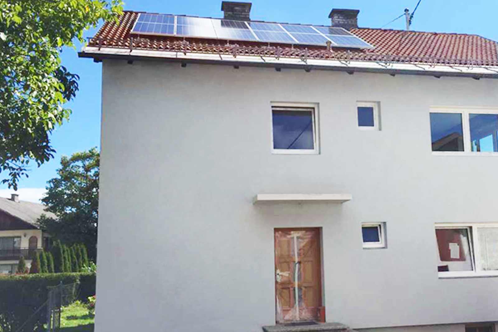Weißes Einfamilienhaus mit Photovoltaikanlage am Dach