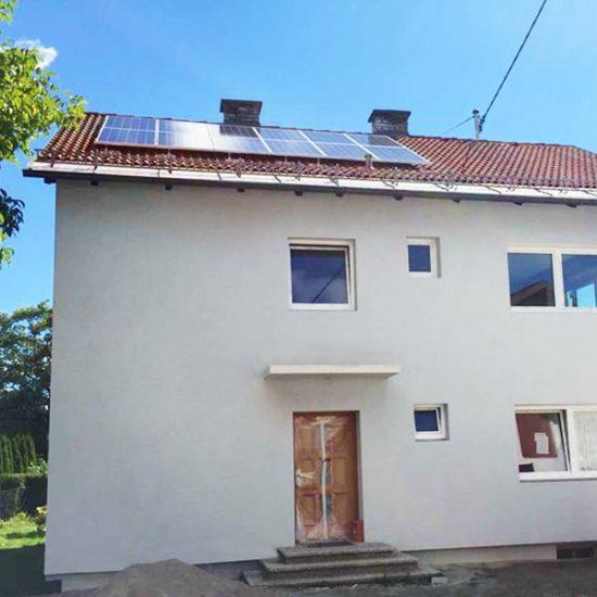 Weißes Haus mit Solaranlage am Dach