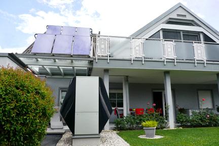 Haus Südseite mit Solaranlage am Dach und Wärmepumpe im Garten
