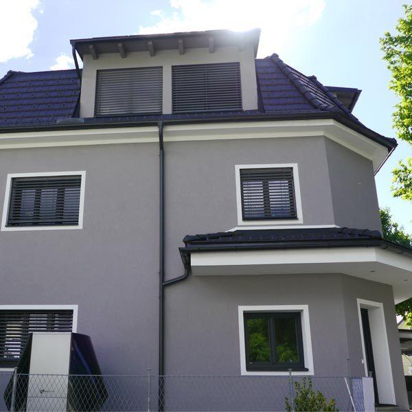 Clicksolar Zweifamilienhaus mit Wärmepumpe im Garten und Sonnenschein