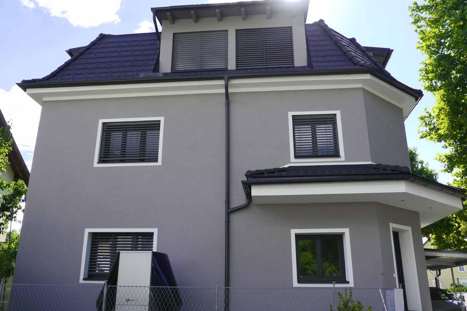 Zweifamilienhaus frontal mit Wärmepumpe und Sonnenschein