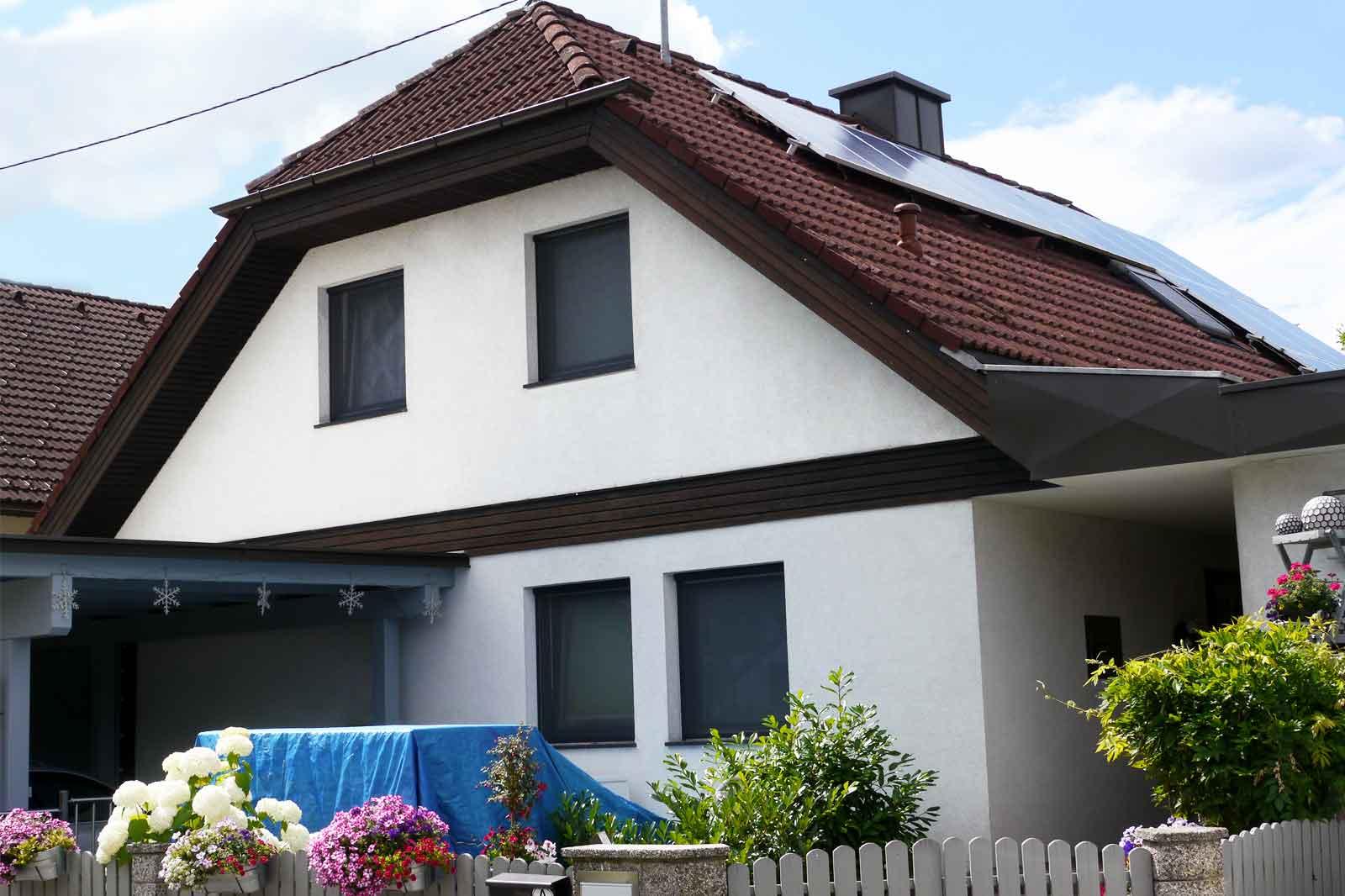 Weißes Einfamilienhaus mit Photovoltaik am Dach