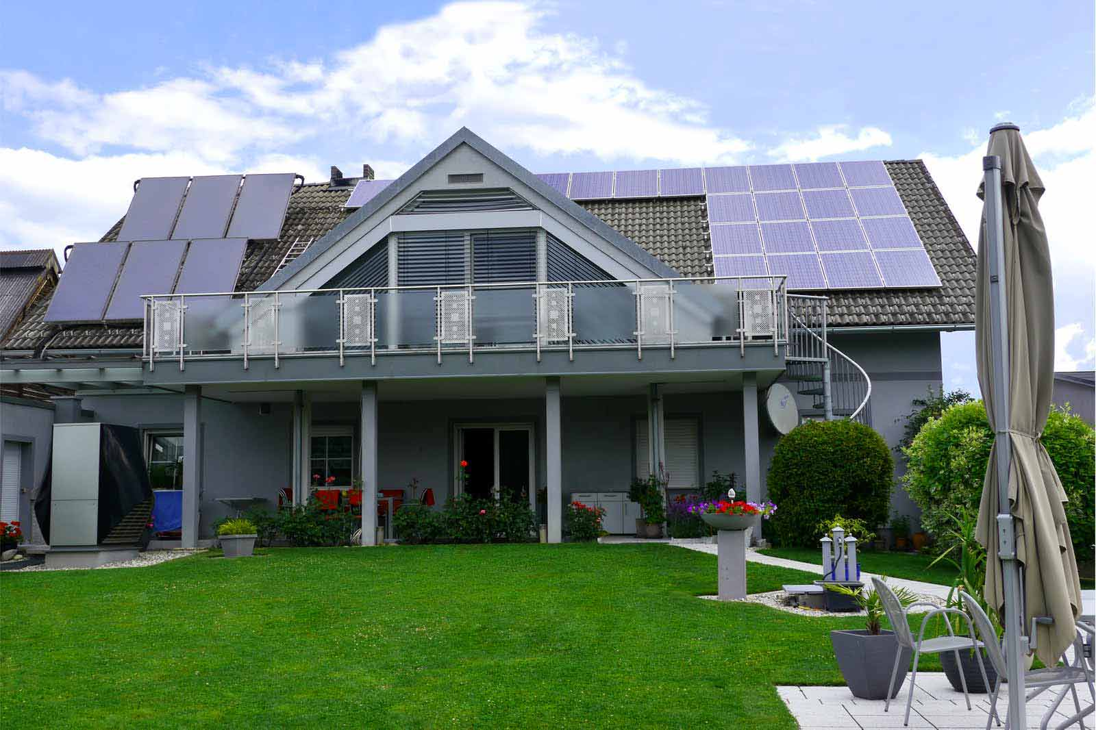 Blaugraues Einfamilienhaus mit Wärmepumpe und Photovoltaik am Dach