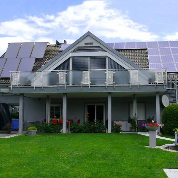 Graublaues Einfamilienhaus mit Photovoltaik und Solaranlage am Dach