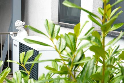 Wärmepumpe vor Hausmauer hinter einer Pflanze