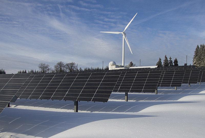 photovoltaik in winterlandschaft mit windkraftwerk
