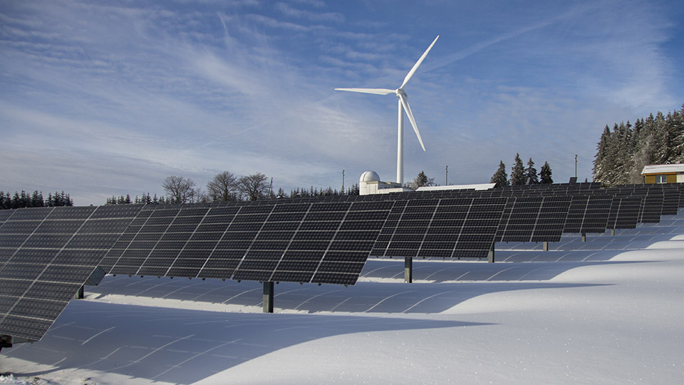 photovoltaik in winterlandschaft mit windkraftwerk